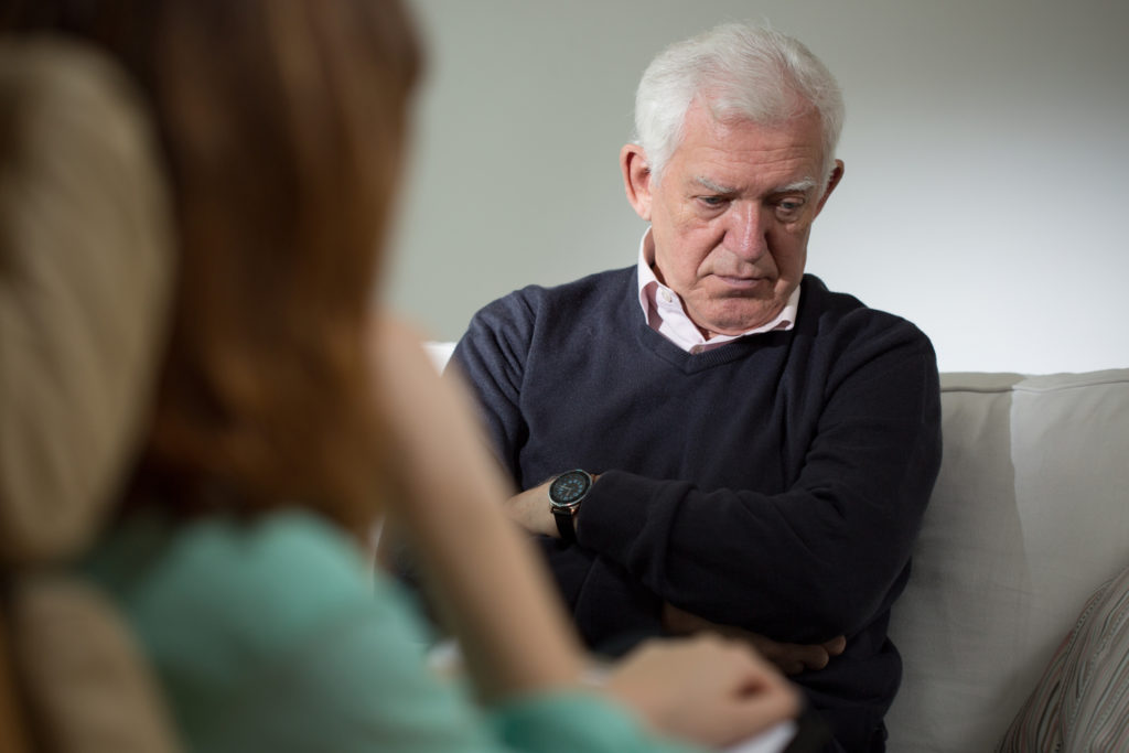 Senior man, looking sad, in a therapy session