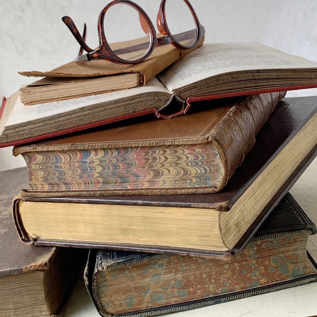 Reading glasses atop a stack of vintage books, some with marbled page edges