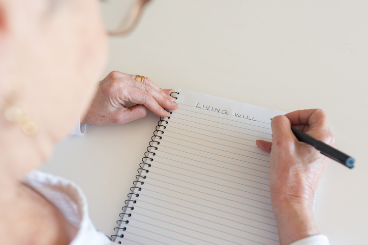 High angle view of older woman writing LIVING WILL in notebook (selective focus)